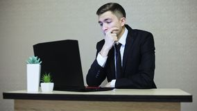 Young businessman with laptop, tired sitting by table at Office stock video footage