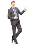 Young businessman leaning against wall and giving thumb up Stock Images