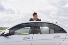 Young businessman leaning on broken down car at countryside Royalty Free Stock Image