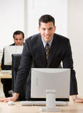 Young businessman leaning on desk. Confident young businessman leaning on desk over computer monitor Royalty Free Stock Photo