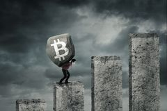 Young businessman lifting symbol of bitcoin. Young businessman lifting a big stone with symbol of bitcoin while climbing on a growth finance graph Stock Photos