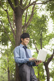 Young businessman lining next to the tree and working on his laptop Royalty Free Stock Photography