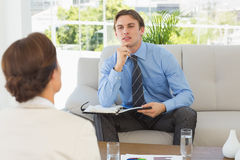 Young businessman listening to colleague sitting on couch Royalty Free Stock Images