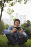 Young businessman listening to music on his MP4 player Stock Photography