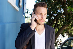Young businessman listening to phone call outside. Portrait of young businessman listening to phone call outside Stock Image
