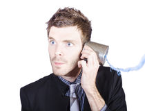 Young businessman listening to telephone can Royalty Free Stock Photo