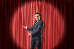 Young businessman lit up by limelight making a presenting gesture against red theater curtain. royalty free stock image