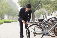 Young businessman locking up his bicycle on a city street in Beijing Royalty Free Stock Photography
