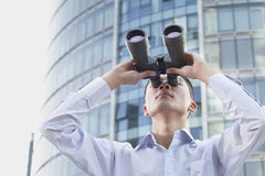 Young Businessman Looking Through Binoculars Royalty Free Stock Photos