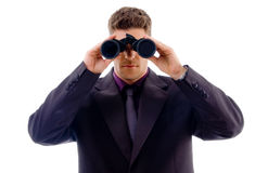 Young businessman looking through binoculars Stock Photo
