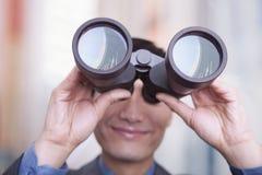 Young businessman looking through binoculars, Beijing Royalty Free Stock Image