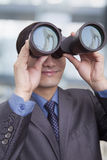 Young businessman looking through binoculars, Beijing Stock Photography