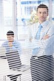 Young businessman looking through blind thinking Stock Images