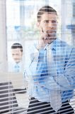 Young businessman looking through blind thinking Royalty Free Stock Photos