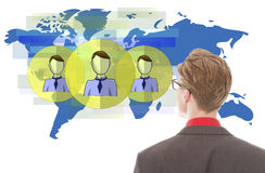 Young businessman looking at blue world map with friends isolated Stock Images