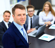 Young businessman looking at the camera on the background of his team Stock Photos