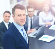 Young businessman looking at the camera on the background of his team Stock Photo