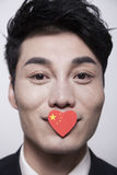 Young businessman looking at the camera with a heart shaped Chinese flag covering his mouth Stock Image
