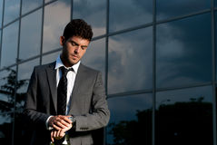 Young businessman looking clock at night Stock Photos