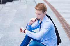 Young businessman looking at the clock and waiting for the client Royalty Free Stock Image