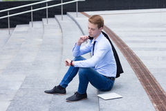 Young businessman looking at the clock and waiting for the client Royalty Free Stock Photo