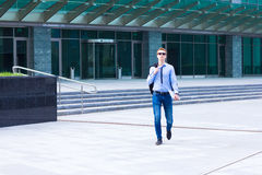 Young businessman looking at the clock and waiting for the clientYoung businessman out of business center Stock Photography