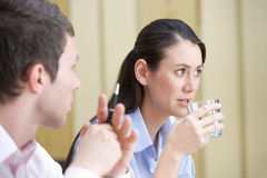 Young businessman looking at colleague with glass of water, close-up Stock Photography