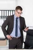 Young businessman is looking concentrated to his smart phone Stock Image
