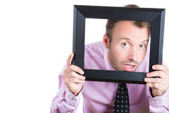 young businessman looking curious and surprised through a picture frame Stock Image