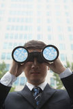Young Businessman looking into the distance through binoculars with clouds and sky in the lenses of the binoculars royalty free stock photo