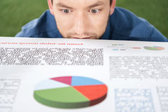 Young businessman looking at documents with business charts and diagrams. Business establishment royalty free stock image