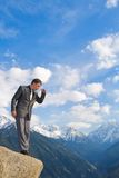 Young businessman looking down from the mountain top Stock Photography