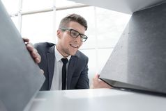 Businessman looking for a folder in the closet. Young businessman looking for a folder in a bookcase on a shelf stock photos