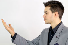 Young businessman looking at his hand. On a white background Royalty Free Stock Images
