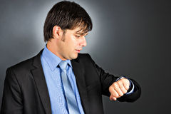 Young businessman looking at his watch Royalty Free Stock Photography