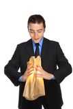 Young businessman looking for hope. Young Businessman looking inside a paperbag stock photo