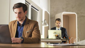 Young Businessman Looking With Interest at a Screen. Two career people in the office. Medium shot. Shot on RED Epic stock footage