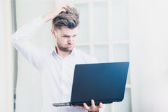 Young businessman looking laptop notebook with shocked negative stress posture Royalty Free Stock Photo