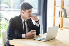 Young businessman looking at laptop screen in modern. Office royalty free stock image