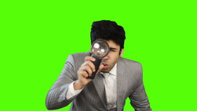 Young businessman looking through a magnifying glass on green background stock video