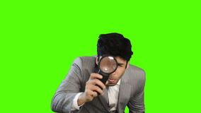 Young businessman looking through a magnifying glass on green background stock footage