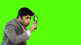 Young businessman looking through a magnifying glass on green background stock video footage