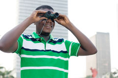 Young businessman looking for new opportunities. The young businessman looks through binoculars to signify that he is looking for paths to succes Royalty Free Stock Image
