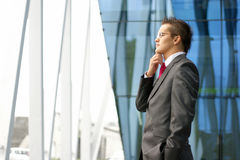 A young businessman is looking outside the window Stock Images