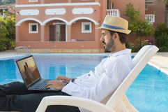 Young businessman looking picture on his laptop by the pool whil Stock Image