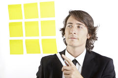 Young businessman looking at postit reminder notes Stock Photo