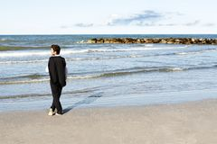 Young businessman looking at sea in contemplation Stock Photo