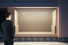 Young businessman looking at showcase. Young businessman looking at empty clean storefront at night. Mock up, 3D Rendering Royalty Free Stock Image