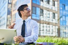 Lunch break. Young businessman looking at sky on summer day while networking and having pizza in urban environment Royalty Free Stock Image