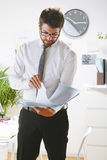 Young businessman looking some papers in office. Royalty Free Stock Images